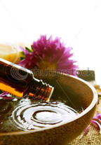 Aromatherapy Bottle of Essential Oil dispesning oil into a wooden container of carrier oil for use as a spa treatment a purple pink flower beside the wooden container