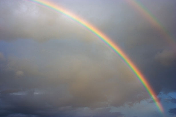 Rainbow in charcoal cloud filled sky public domain