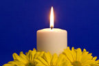 burning white candle surrounded by yellow daisies with blue ground